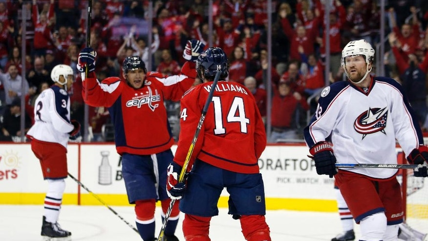 Washington Capitals left wing Alex Ovechkin (8), from Russia, and right wing Justin Williams (14) celebrate Williams' goal in the first period of an NHL hockey game against the Columbus Blue Jackets, Monday, March 28, 2016, in Washington. (AP Photo/Alex Brandon)