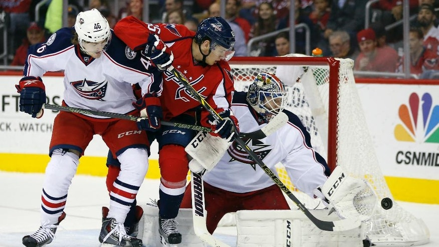 Columbus Blue Jackets defenseman Dean Kukan (46) defends against Washington Capitals left wing Andre Burakovsky (65), from Austria, with Columbus Blue Jackets goalie Sergei Bobrovsky (72), from Russia, deflecting the puck, in the first period of an NHL hockey game, Monday, March 28, 2016, in Washington. (AP Photo/Alex Brandon)
