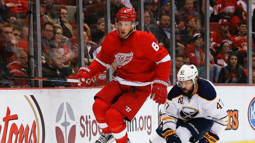 Detroit Red Wings left wing Justin Abdelkader (8) jumps over the stick of Buffalo Sabres defenseman Zach Bogosian (47) in the second period of an NHL hockey game, Monday, March 28, 2016, in Detroit. (AP Photo/Paul Sancya)