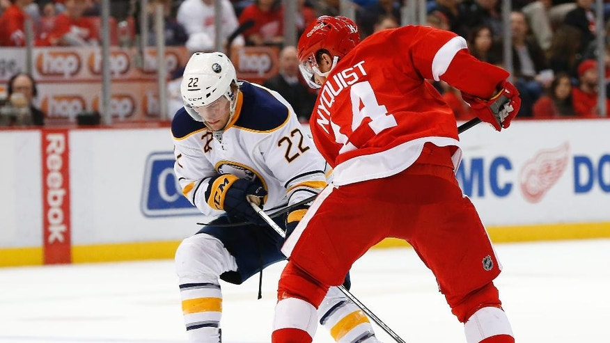 Buffalo Sabres left wing Johan Larsson (22) and Detroit Red Wings center Gustav Nyquist (14) battle for the puck in the second period of an NHL hockey game, Monday, March 28, 2016, in Detroit. (AP Photo/Paul Sancya)