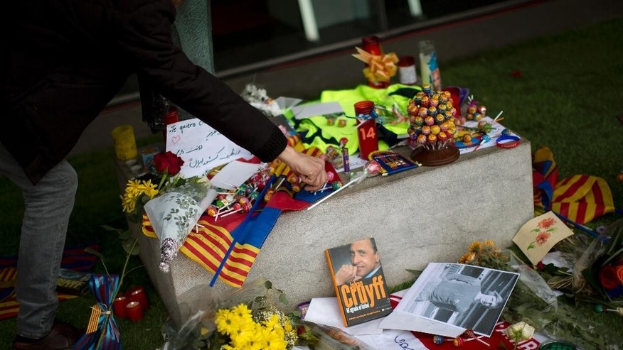 "A FC Barcelona supporter places a memento in respect to the late Dutch soccer great Johan Cruyff at the Camp Nou stadium in Barcelona, Spain, Saturday, March 26, 2016. Dutch soccer great Johan Cruyff, who revolutionized the game as the personification of ""Total Football,"" has died. He was 68.  (AP Photo/Emilio Morenatti)"