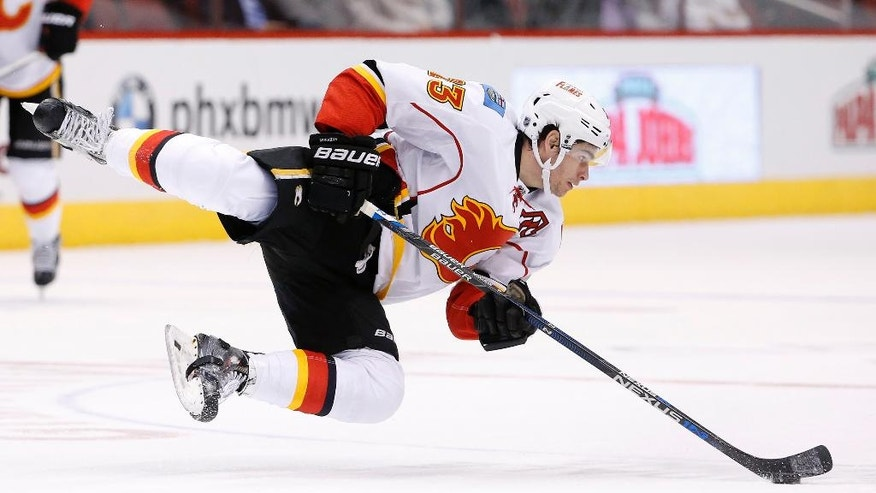 Calgary Flames' Sean Monahan falls to the ice after trying to change direction and keep control of the puck during the first period of an NHL hockey game against the Arizona Coyotes, Monday, March 28, 2016, in Glendale, Ariz. (AP Photo/Ross D. Franklin)
