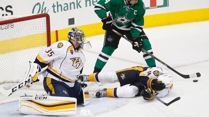 Dallas Stars left wing Jamie Benn (14) looks for the shot on Nashville Predators goalie Pekka Rinne  (35) as defenseman Ryan Ellis (4) tries to avoid injury during the first period of an NHL hockey game Tuesday, March 29, 2016, in Dallas.  (AP Photo/Tim Sharp)