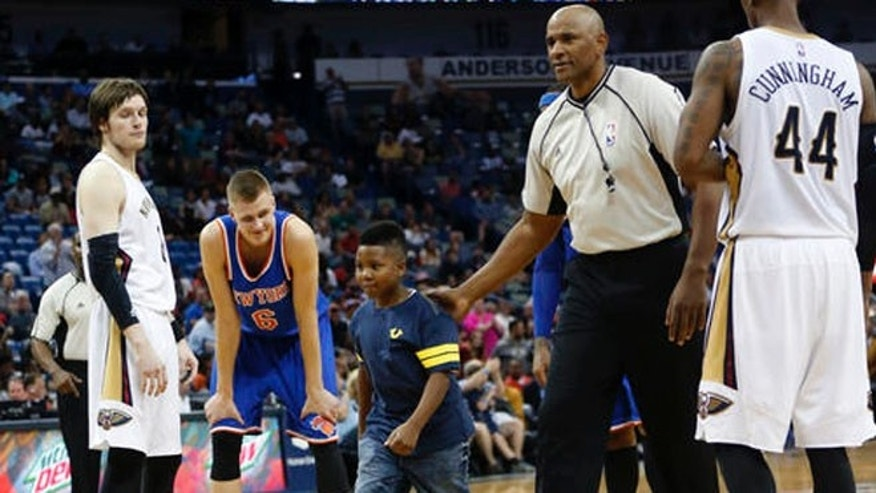 A young boy is sent back to the stands by the referee after he ran onto the court in the second half of an NBA basketball game between the New Orleans Pelicans and the New York Knicks in New Orleans, Monday, March 28, 2016. The Pelicans won 99-91. (AP Photo/Gerald Herbert)