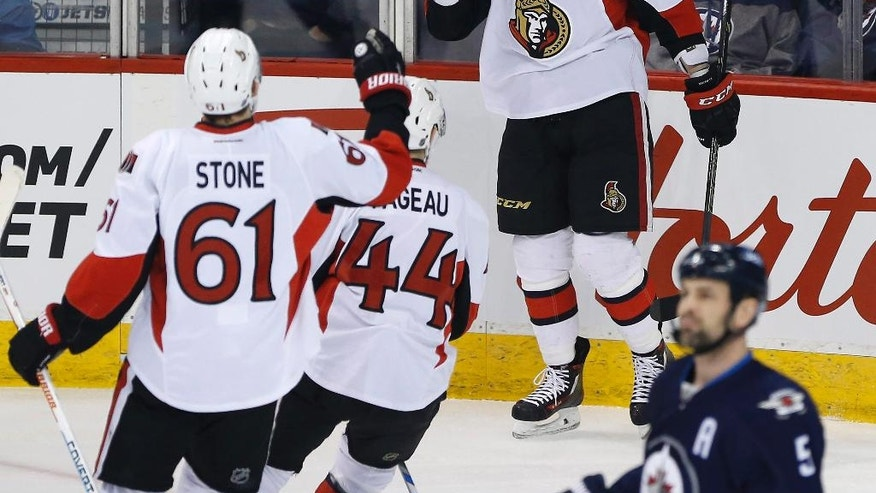 Ottawa Senators' Mark Stone (61), Jean-Gabriel Pageau (44) and Zack Smith (15) celebrate Smith's goal against the Winnipeg Jets during the first period of an NHL hockey game Tuesday, March 30, 2016, in Winnipeg, Manitoba. (John Woods/The Canadian Press via AP)