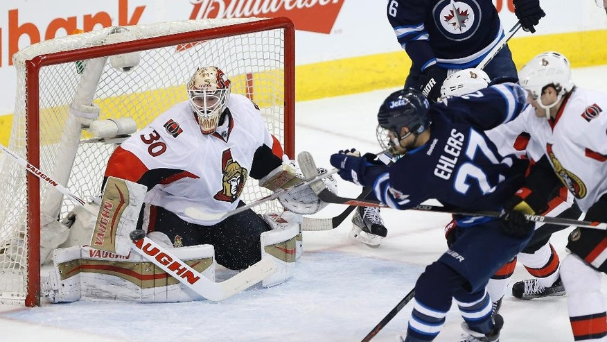 Ottawa Senators goaltender Andrew Hammond (30) saves the shot from Winnipeg Jets' Nikolaj Ehlers (27) as Senators' Chris Wideman (45) and Bobby Ryan (6) defend during the first period of an NHL hockey game Tuesday, March 30, 2016, in Winnipeg, Manitoba. (John Woods/The Canadian Press via AP)
