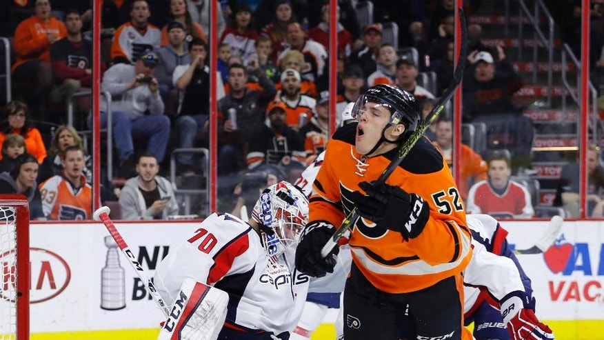 Philadelphia Flyers' Nick Cousins, center, is sent flying after a hit from Washington Capitals' Tom Wilson, right, in front of goalie Braden Holtby during the second period of an NHL hockey game, Wednesday, March 30, 2016, in Philadelphia. (AP Photo/Matt Slocum)