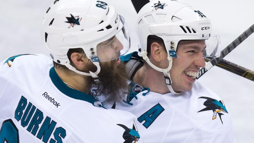 San Jose Sharks' Brent Burns, left, and Logan Couture celebrate Couture's third goal against the Vancouver Canucks, during the third period of an NHL hockey game Tuesday, March 29, 2016, in Vancouver, British Columbia. (Darryl Dyck/The Canadian Press via AP)