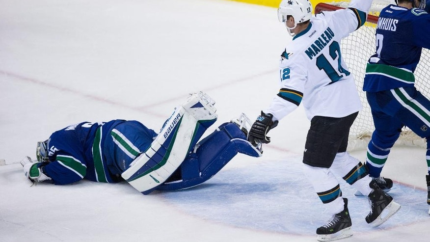 San Jose Sharks' Patrick Marleau, right, celebrates teammate Logan Couture's second goal as Vancouver Canucks goalie Jacob Markstrom, of Sweden, lies on the ice during the third period of an NHL hockey game Tuesday, March 29, 2016, in Vancouver, British Columbia. (Darryl Dyck/The Canadian Press via AP)
