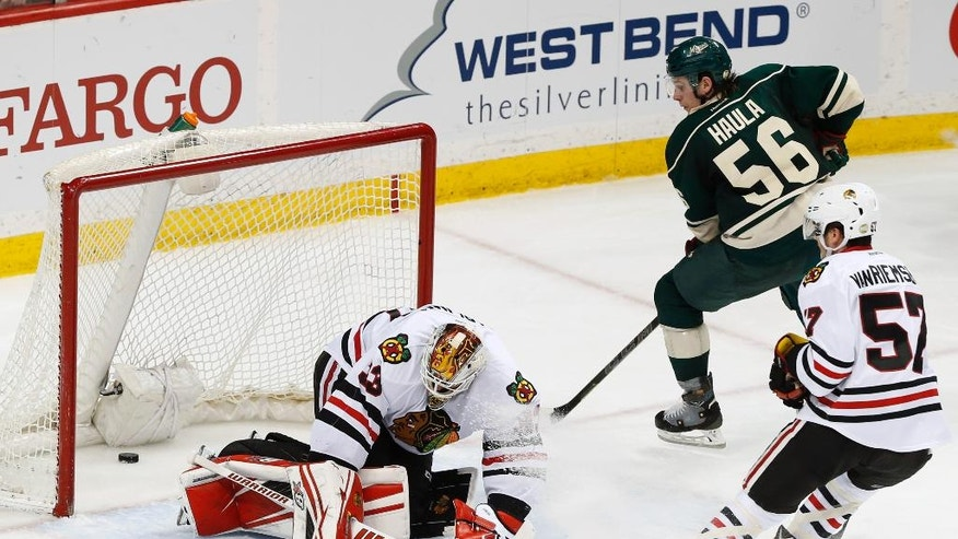 Minnesota Wild's Erik Haula, top right,  of Finland, scores against Chicago Blackhawks goalie Scott Darling, left,  in the third period of an NHL hockey game Tuesday, March 29, 2016, in St. Paul, Minn. The Wild won 4-1. (AP Photo/Jim Mone)