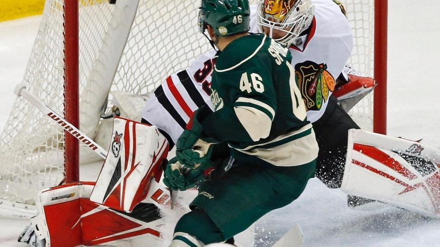 Minnesota Wild's Jared Spurgeon, left,  scores against Chicago Blackhawks goalie Scott Darling in the third period of an NHL hockey game Tuesday, March 29, 2016, in St. Paul, Minn. The Wild won 4-1. (AP Photo/Jim Mone)