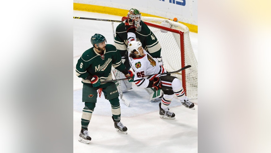 Chicago Blackhawks' Andrew Shaw, right, loses his balance as Minnesota Wild's Marco Scandella, left, defends along with goalie Devan Dubnyk in the third period of an NHL hockey game Tuesday, March 29, 2016, in St. Paul, Minn. The Wild won 4-1. (AP Photo/Jim Mone)