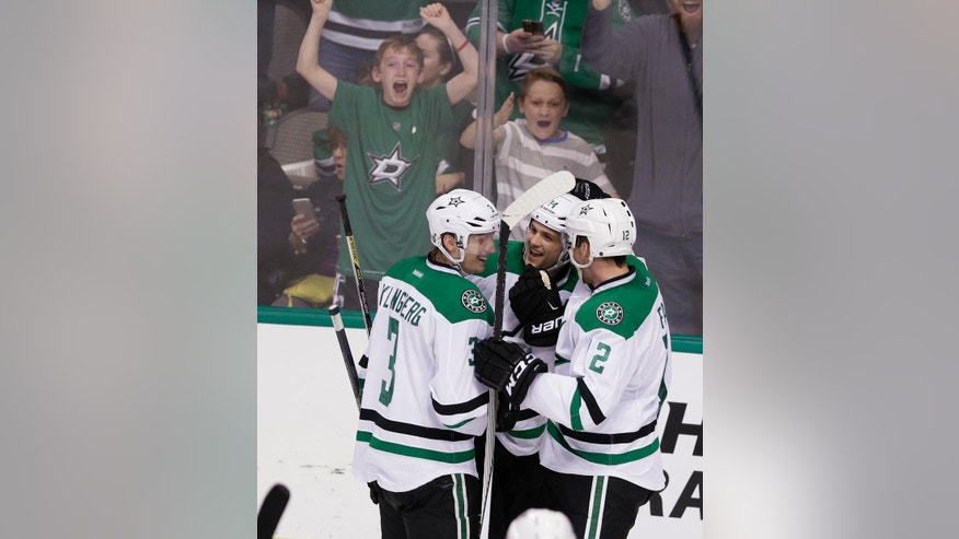 Dallas Stars left wing Jamie Benn, center celebrates scoring a goal with teammates John Klingberg (3) and Kris Russell (2) during the second period of an NHL hockey game against the Arizona Coyotes on Thursday, March 31, 2016, in Dallas. (AP Photo/LM Otero)