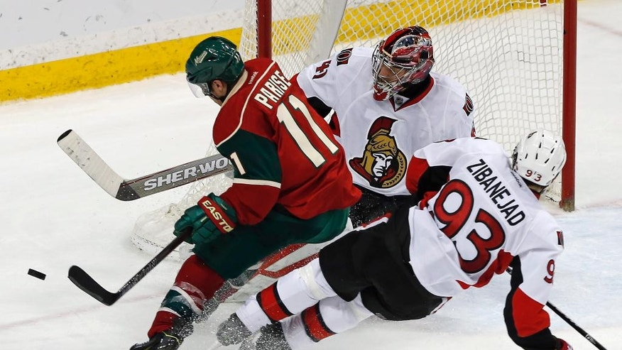 Ottawa Senators' Mika Zibanejad, right, of Sweden, falls as he helps break up a scoring attempt by Minnesota Wild's Zach Parise in the third period of an NHL hockey game Thursday, March 31, 2016, in St. Paul, Minn. The Senators won 3-2. In goal is Craig Anderson. (AP Photo/Jim Mone)