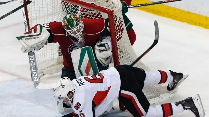Ottawa Senators' Bobby Ryan, bottom, falls after hitting the net which tilts over Minnesota Wild goalie Devan Dubnyk in the first period of an NHL hockey game Thursday, March 31, 2016, in St. Paul, Minn. (AP Photo/Jim Mone)