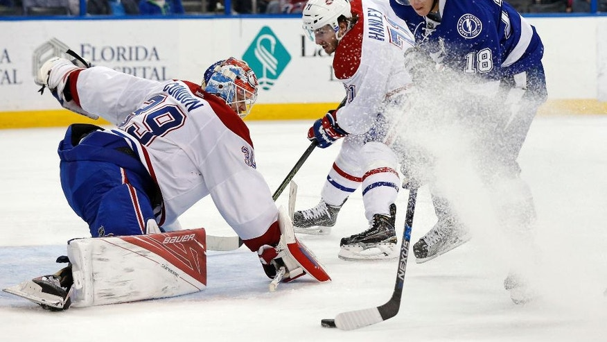 Tampa Bay Lightning's Ondrej Palat (18), of the Czech Republic, shoots on Montreal Canadiens goalie Mike Condon as Joel Hanley defends during the second period of an NHL hockey game Thursday, March 31, 2016, in Tampa, Fla. Palat was hooked by Hanley on the play and awarded a penalty shot. (AP Photo/Mike Carlson)