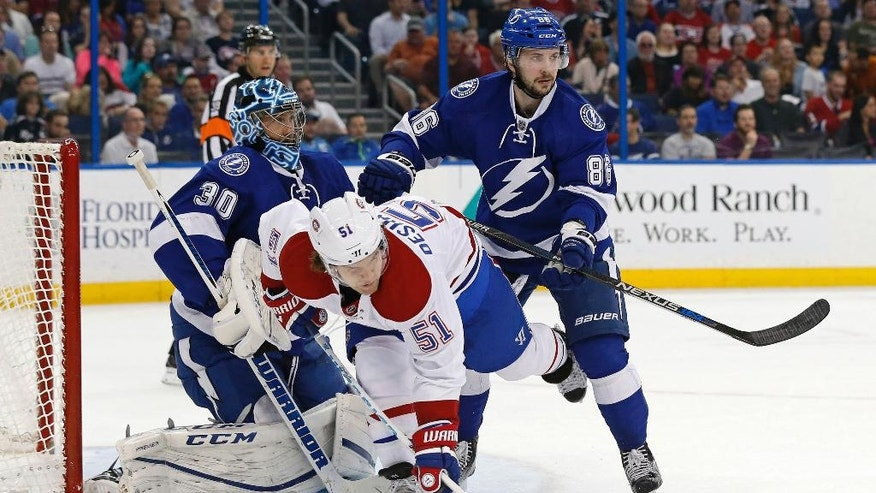 Tampa Bay Lightning's Jonathan Marchessault, right,checks Montreal Canadiens' David Desharnais in front of goalie Ben Bishop during the first period of an NHL hockey game Thursday, March 31, 2016, in Tampa, Fla. (AP Photo/Mike Carlson)