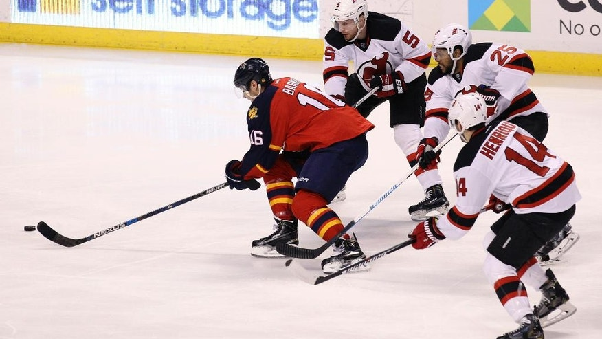 Florida Panthers' Aleksander Barkov, left,  of Finland, moves the puck as New Jersey Devils' Adam Larsson (5), of Sweden, Devante Smith-Pelly (25) and Adam Henrique (14) defend during the first period of an NHL hockey game, Thursday, March 31, 2016, in Sunrise, Fla. (AP Photo/Luis M. Alvarez)