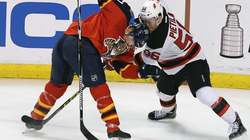 Florida Panthers' Brian Campbell, left,  and New Jersey Devils' Blake Pietila, right, battle for the puck during the first period of an NHL hockey game, Thursday, March 31, 2016, in Sunrise, Fla. (AP Photo/Luis M. Alvarez)
