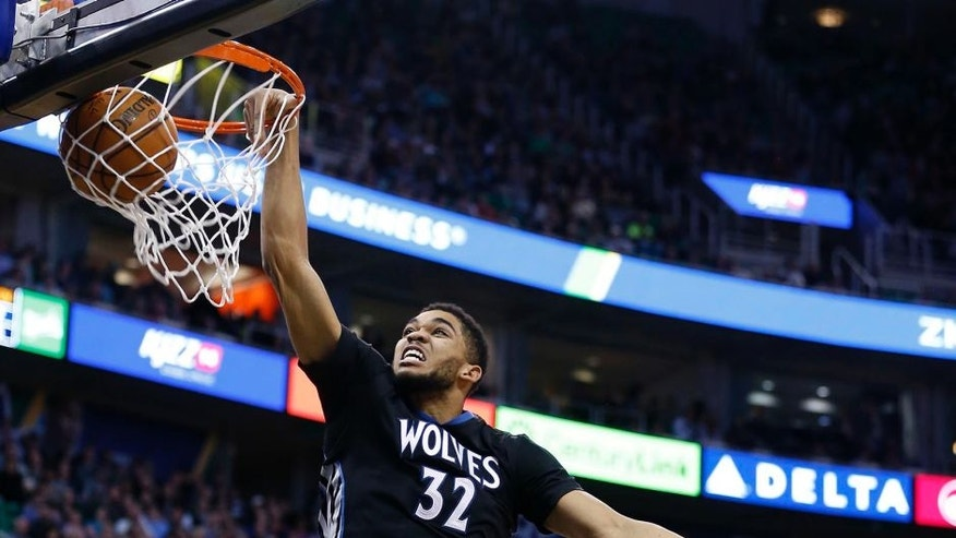 Jan 29, 2016; Salt Lake City, UT, USA; Minnesota Timberwolves center Karl-Anthony Towns (32) dunks the ball in the second quarter against Utah Jazz forward Derrick Favors (15) and center Rudy Gobert (27) at Vivint Smart Home Arena. Mandatory Credit: Jeff Swinger-USA TODAY Sports
