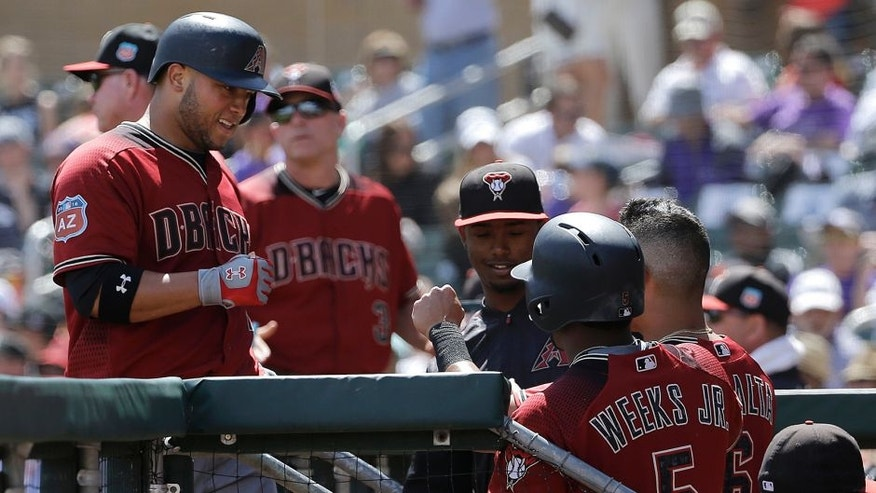 Arizona Diamondbacks' Welington Castillo, left, is congratulated after hitting a home run against the Colorado Rockies during the fourth inning of a spring training baseball game in Scottsdale, Ariz., Thursday, March 31, 2016. (AP Photo/Jeff Chiu)
