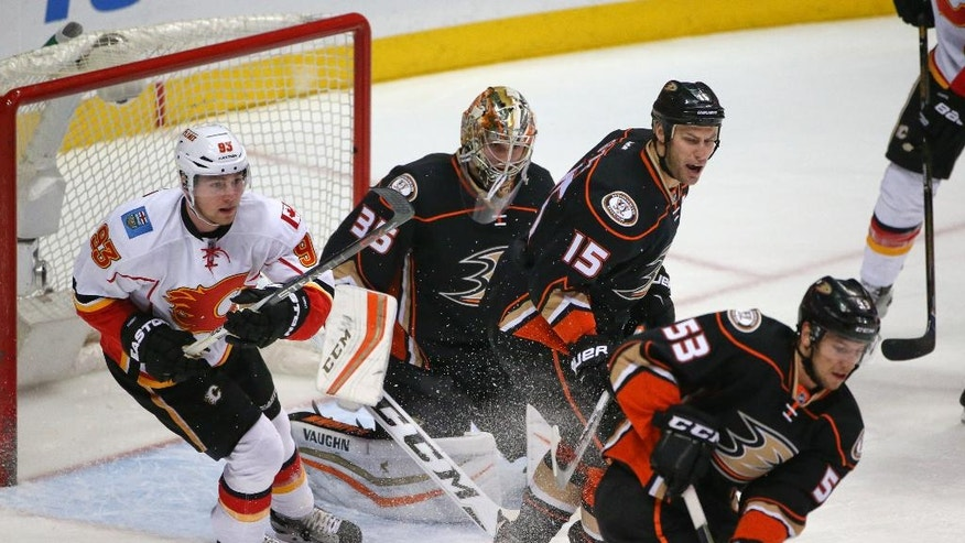 Anaheim Ducks goalie John Gibson, center Ryan Getzlaf, center, and left wing Jakob Silfverberg turn away a Calgary Flames charge by center Sam Bennett during the first period of an NHL hockey game Wednesday, March 30, 2016, in Anaheim, Calif. (AP Photo/Lenny Ignelzi)