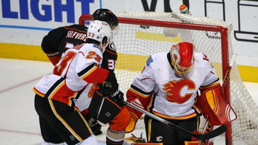 Calgary Flames goalie Jonas Hiller stops a shot attempt by Anaheim Ducks left wing Jakob Silfverberg but the puck came loose and Silfverberg backhanded a shot into the net during the first period of a NHL hockey game Wednesday, March 30, 2016, in Anaheim, Calif. (AP Photo/Lenny Ignelzi)