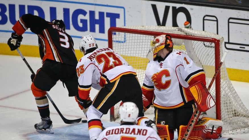 Anaheim Ducks defenseman Clayton Stoner flips a backhand shot past Calgary Flames goalie Jonas Hiller and center Sean Monahan during the first period of a NHL hockey game Wednesday, March 30, 2016, in Anaheim, Calif. (AP Photo/Lenny Ignelzi)