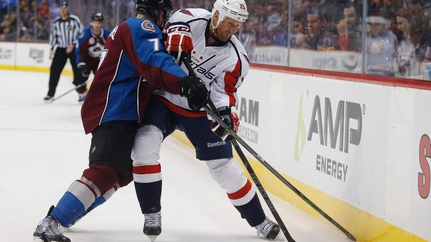 Washington Capitals left wing Jason Chimera, right, tries to control the puck as Colorado Avalanche center John Mitchell defends in the second period of an NHL hockey game Friday, April 1, 2016, in Denver. (AP Photo/David Zalubowski)