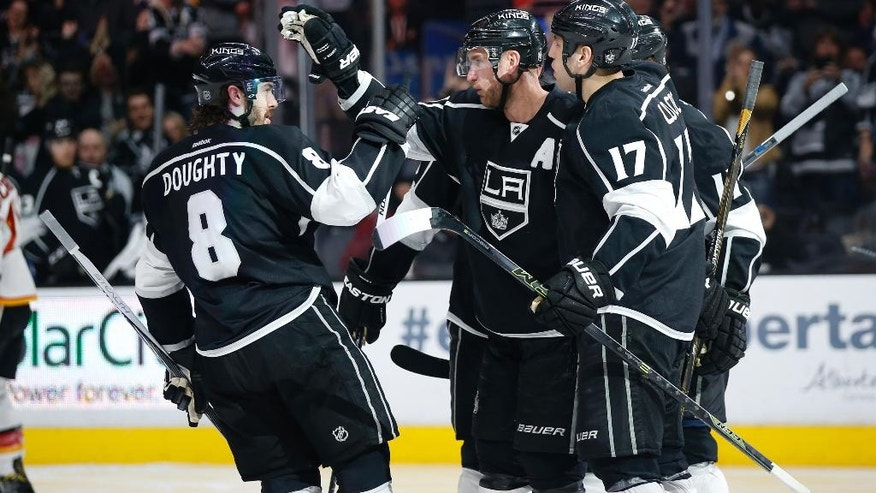 Los Angeles Kings center Jeff Carter, second from left, celebrates his power-play goal with teammates, including Drew Doughty, left, and Milan Lucic, right, against the Calgary Flames during the second period of an NHL hockey game, Thursday, March 31, 2016, in Los Angeles. (AP Photo/Danny Moloshok)
