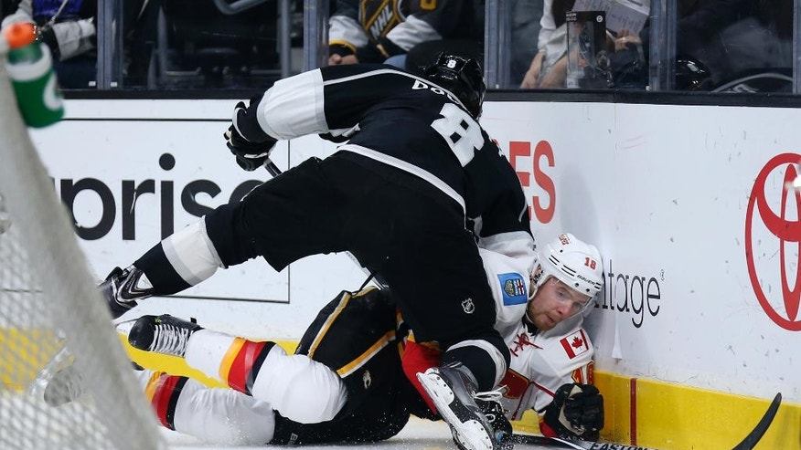 Calgary Flames center Matt Stajan, bottom, reaches for the puck while Los Angeles Kings defenseman Drew Doughty checks him during the first period of an NHL hockey game Thursday, March 31, 2016, in Los Angeles. (AP Photo/Danny Moloshok)