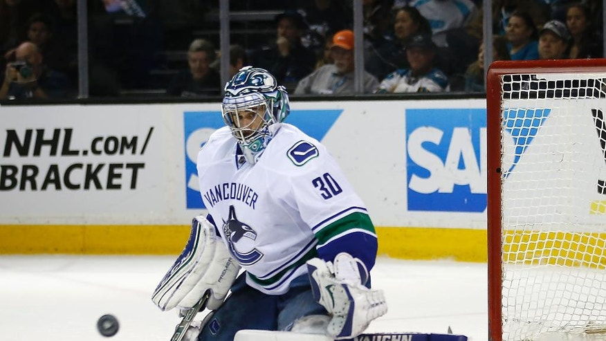 Vancouver Canucks goalie Ryan Miller (30) blocks a shot from San Jose Sharks during the first period of an NHL hockey game Thursday, March 31, 2016, in San Jose, Calif. (AP Photo/Tony Avelar)