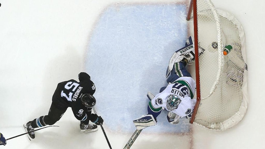 Vancouver Canucks goalie Ryan Miller (30) blocks a shot from San Jose Sharks center Tommy Wingels (57) during the first period of an NHL hockey game Thursday, March 31, 2016, in San Jose, Calif. (AP Photo/Tony Avelar)