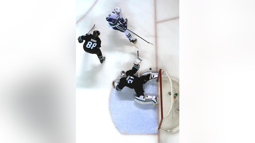 San Jose Sharks goalie Martin Jones (31) stretches out to block a shot from Vancouver Canucks left wing Alex Burrows, top, during the second period of an NHL hockey game Thursday, March 31, 2016, in San Jose, Calif. Sharks defenseman Brent Burns is at left. (AP Photo/Tony Avelar)