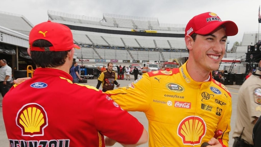 Sprint Cup driver Joey Logano, right, is congratulated by a crew member after wining the pole for Sunday's STP 500 Sprint Cup race at the Martinsville Speedway Friday, April 1, 2016 in Martinsville, Va. (AP Photo/Steve Helber)