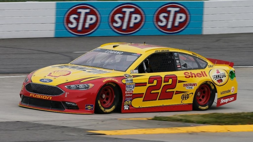 Diver Joey Logano (22) runs through turn two during qualifying for Sunday's NASCAR Sprint Cup auto race at the Martinsville Speedway Friday, April 1, 2016 in Martinsville, Va. (AP Photo/Steve Helber)