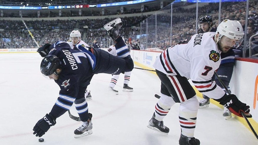 Winnipeg Jets' Ben Chiarot, left, is checked by Chicago Blackhawks' Brent Seabrook, right front, as Blackhawks' Marcus Kruger (22) picks up the loose puck during the second period of an NHL hockey game Friday, April 1, 2016, in Winnipeg, Manitoba. (John Woods/The Canadian Press via AP)