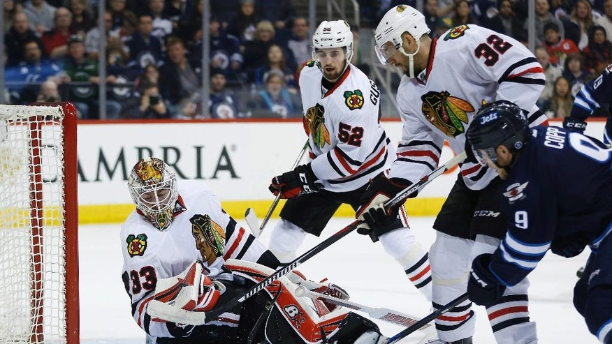The puck drops behind Chicago Blackhawks goaltender Scott Darling (33) as Erik Gustafsson (52) and Michal Rozsival (32) defend Winnipeg Jets' Andrew Copp (9) during the second period of an NHL hockey game Friday, April 1, 2016, in Winnipeg, Manitoba. (John Woods/The Canadian Press via AP)