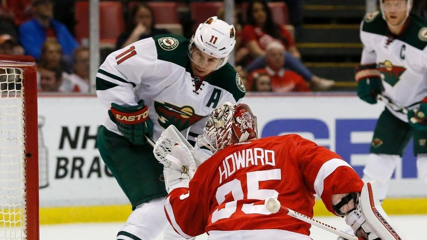 Minnesota Wild's Zach Parise (11) tries to take a shot on goal against Detroit Red Wings' Jimmy Howard (35) during the first period of an NHL hockey game Friday, April 1, 2016, in Detroit. (AP Photo/Duane Burleson)