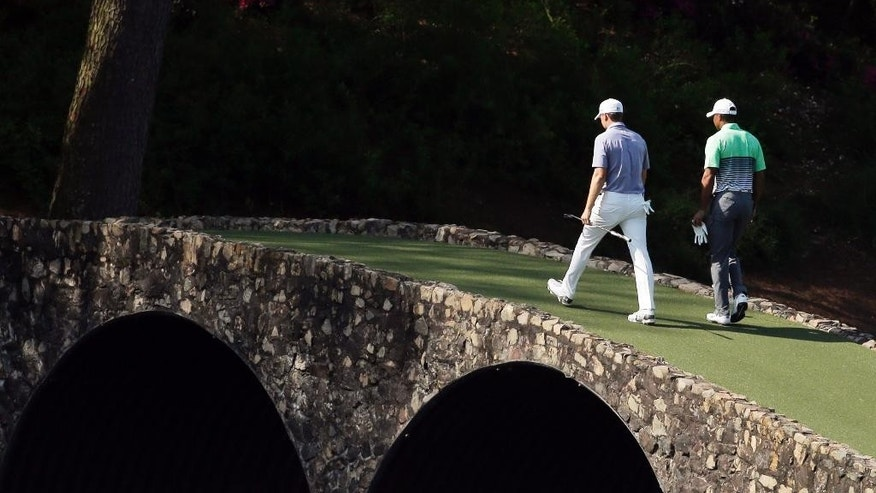 ADVANCE FOR WEEKEND EDITIONS, APRIL 2-3 - In this April 8, 2015, file photo, Tiger Woods, right, walks across the Ben Hogan Bridge with Jordan Spieth during a practice round for the Masters golf tournament in Augusta, Ga. His intelligence on the golf course might be a big reason that Spieth last year became the youngest player in nearly a century to win two majors at age 21. (AP Photo/Chris Carlson, File)