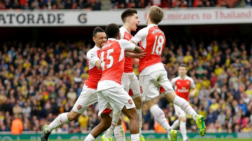 Arsenal's Hector Bellerin, center, jumps as he celebrates scoring his side's third goal during the English Premier League soccer match between Arsenal and Watford at the Emirates Stadium in London, Saturday, April 2, 2016.  (AP Photo/Matt Dunham)