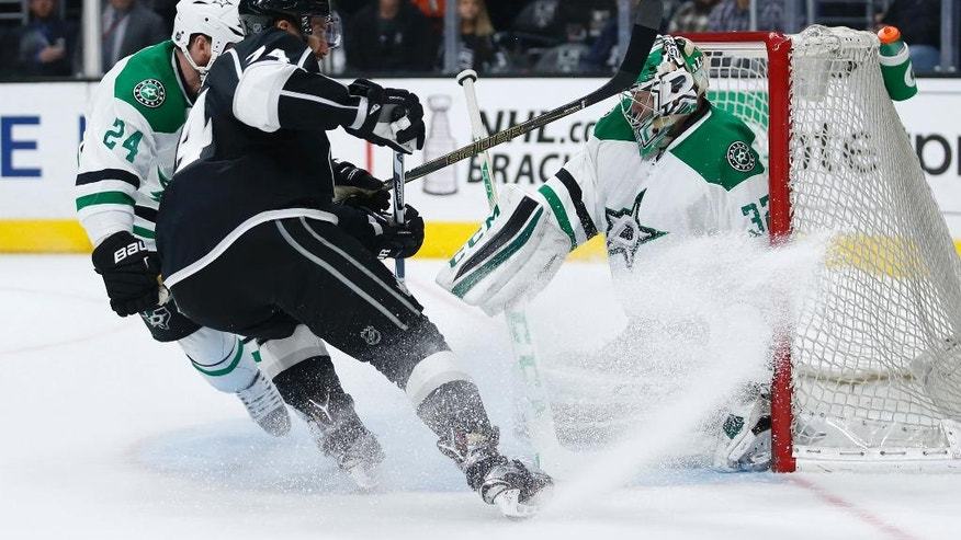 Los Angeles Kings left wing Dwight King, center, looks for a rebound while Dallas Stars goalie Kari Lehtonen protects the net and Stars' Jordie Benn, left, also defends during the second period of an NHL hockey game, Saturday, April 2, 2016, in Los Angeles. (AP Photo/Danny Moloshok)
