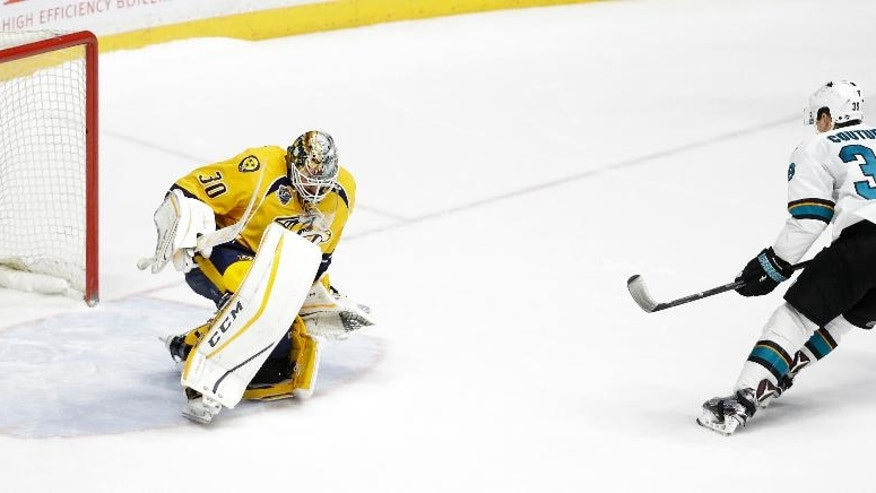 San Jose Sharks center Logan Couture (39) scores the winning goal against Nashville Predators goalie Carter Hutton (30) during a shootout at an NHL hockey game Saturday, April 2, 2016, in Nashville, Tenn. The Sharks won 3-2. (AP Photo/Mark Humphrey)
