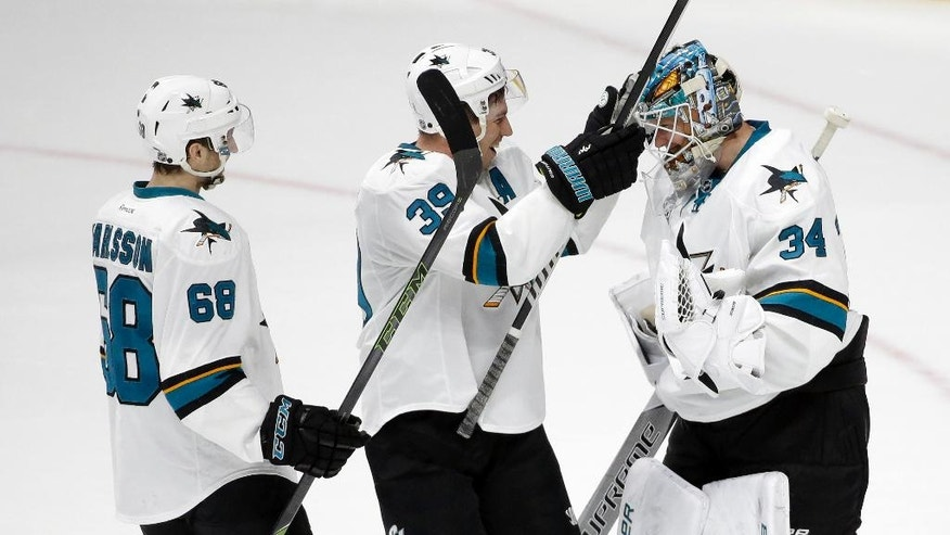 San Jose Sharks goalie James Reimer (34) is congratulated by Logan Couture (39) and Melker Karlsson (68), of Sweden, after defeating the Nashville Predators in a shootout at an NHL hockey game Saturday, April 2, 2016, in Nashville, Tenn. The Sharks won 3-2. (AP Photo/Mark Humphrey)