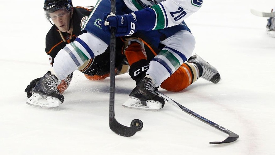Vancouver Canucks left wing Chris Higgins, right, controls the puck against Anaheim Ducks defenseman Josh Manson, left, during the first period of an NHL hockey game in Anaheim, Calif., Friday, April 1, 2016. (AP Photo/Alex Gallardo)