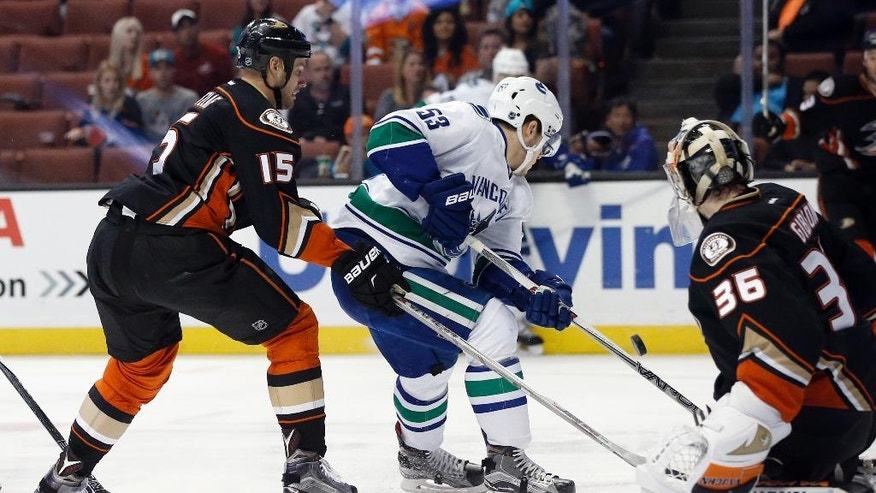 Vancouver Canucks center Bo Horvat (53) deflects the puck towards Anaheim Ducks goalie John Gibson (36) with center Ryan Getzlaf (15) defending during the first period of an NHL hockey game in Anaheim, Calif., Friday, April 1, 2016. (AP Photo/Alex Gallardo)