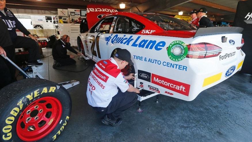 Members of the Wood Brothers race team gets the car ready for the final practice for Sunday's NASCAR Sprint Cup Series auto race at the Martinsville Speedway Saturday, April 2, 2016 in Martinsville, Va. (AP Photo/Steve Helber)