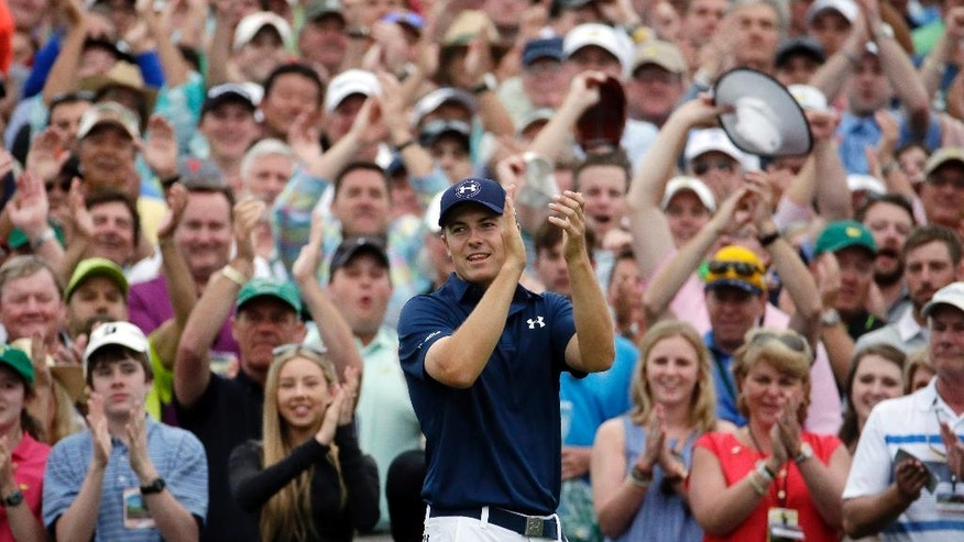 ADVANCE FOR WEEKEND EDITIONS, APRIL 2-3 - In this April 12, 2016, file photo, Jordan Spieth applauds after winning the Masters golf tournament in Augusta, Ga. His intelligence on the golf course might be a big reason that Spieth last year became the youngest player in nearly a century to win two majors at age 21. (AP Photo/Charlie Riedel, File_