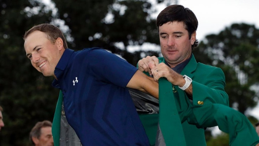 ADVANCE FOR WEEKEND EDITIONS, APRIL 2-3 - In this April 12, 2016, file photo, Bubba Watson, right, helps Jordan Spieth put on his green jacket for the second time after winning the Masters golf tournament in Augusta, Ga. His intelligence on the golf course might be a big reason that Spieth last year became the youngest player in nearly a century to win two majors at age 21. (AP Photo/Darron Cummings, File)