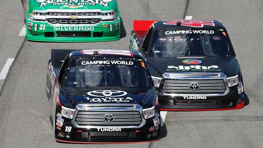 Kyle Busch (18) passes Ben Rhodes (41) to lead the NASCAR Camping World Truck race at the Martinsville Speedway Saturday, April 2, 2016 in Martinsville, Va. (AP Photo/Steve Helber)